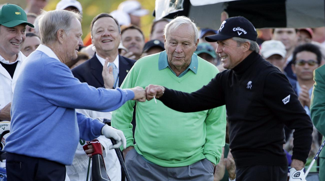 FILE - In this April 10, 2014, file photo, Arnold Palmer, center, watches as Jack Nicklaus, left, and Gary Player touch fists after Palmer hit his ceremonial drive on the first tee before the first round of the Masters golf tournament, in Augusta, Ga. Arn