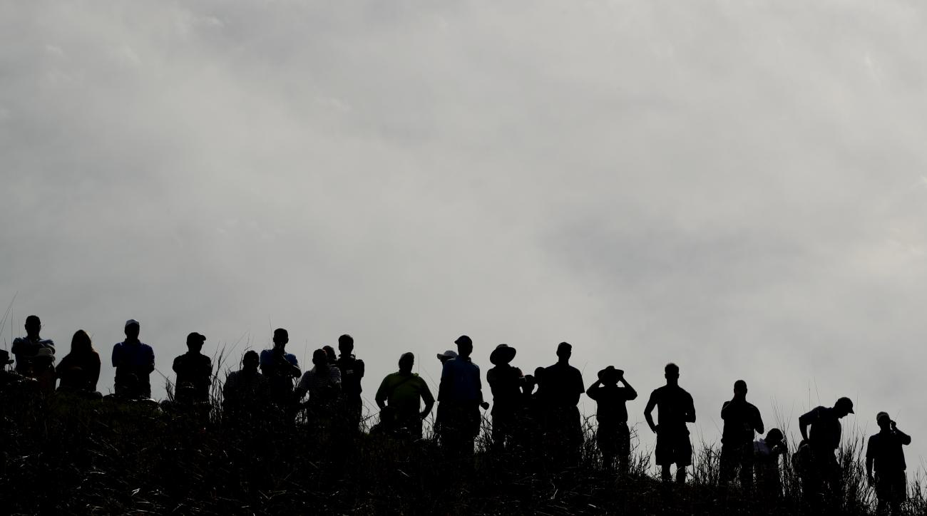 Fans watch from a hill overlooking the 16th green during quarterfinal round play at the Dell Match Play Championship golf tournament at Austin County Club Saturday, March 26, 2016, in Austin, Texas. (AP Photo/Charlie Riedel)