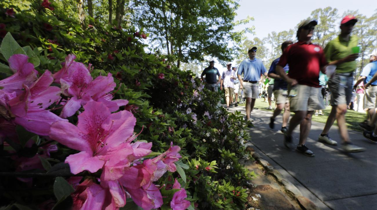 Spectators walk past azaleas on the 16th hole during a practice round for the Masters golf tournament, Monday, April 4, 2016, in Augusta, Ga. (AP Photo/Chris Carlson)
