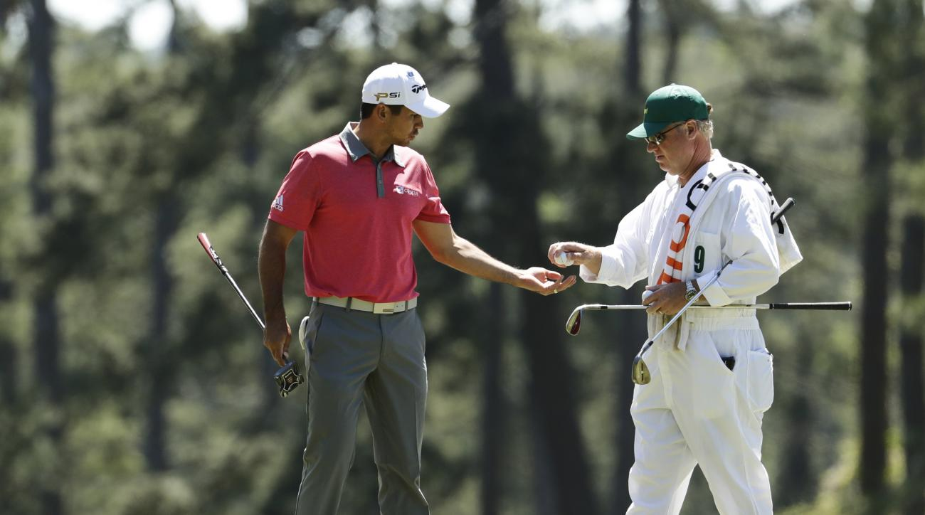Jason Day, of Australia, gets golf balls from his caddie Colin Swatton during a practice round for the Masters golf tournament, Tuesday, April 5, 2016, in Augusta, Ga. (AP Photo/Charlie Riedel)