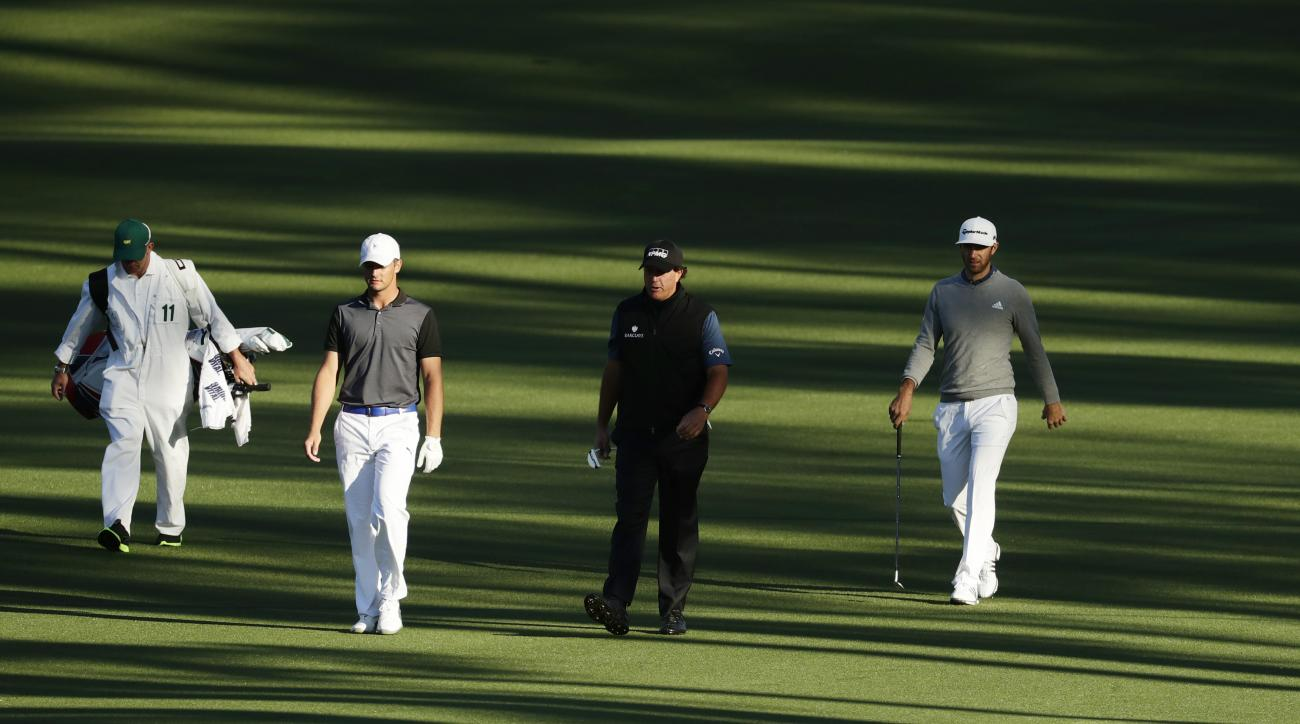 CORRECTS SPELLING TO DeCHAMBEAU, INSTEAD OF DeCHAMBEA - Amateur Bryson DeChambeau, second left, walks with Phil Mickelson and Dustin Johnson, right, down the second fairway during a practice round for the Masters golf tournament, Tuesday, April 5, 2016, i