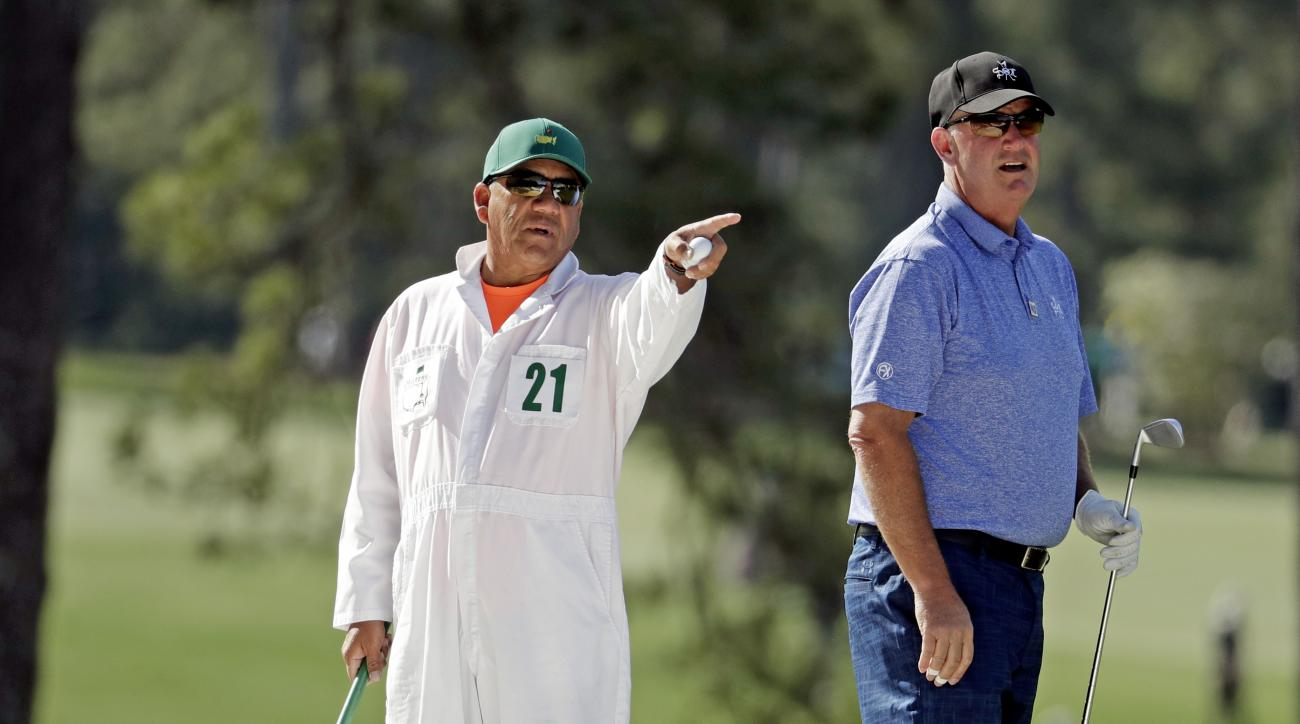 Caddie Eseban Tolledo gives Sandy Lyle, of Scotland, advice on the first hole during a practice round for the Masters golf tournament Wednesday, April 6, 2016, in Augusta, Ga. (AP Photo/Charlie Riedel)