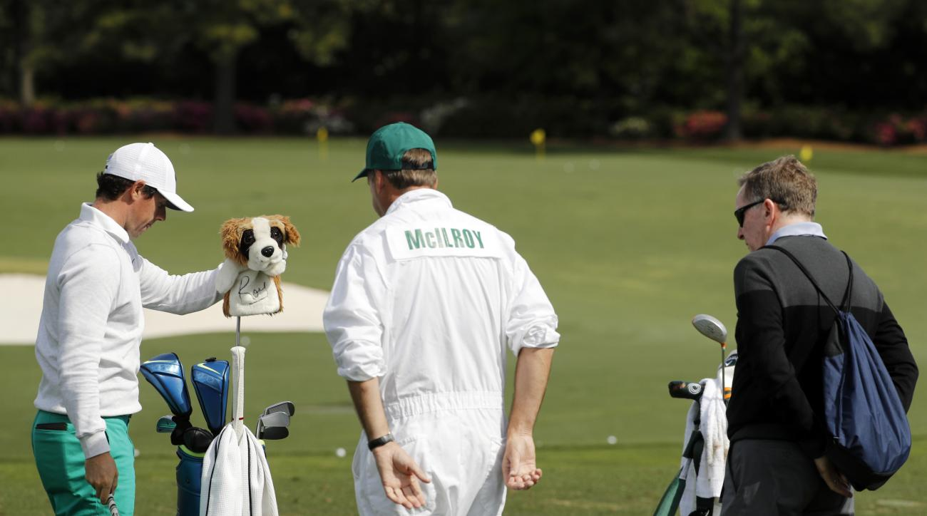 Coach Michael Bannon, right and caddie Jean-Paul Fitzgerald watch as Rory McIlroy, of Northern Ireland, prepares to hit on the driving range during a practice round for the Masters golf tournament Wednesday, April 6, 2016, in Augusta, Ga. (AP Photo/Chris