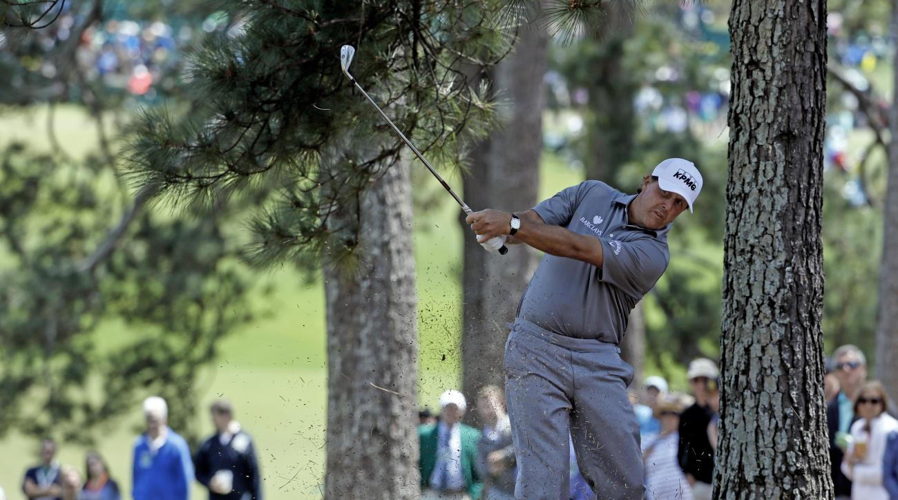 Phil Mickelson hits from the pine straw on the first hole during the second round of the Masters golf tournament Friday, April 8, 2016, in Augusta, Ga. (AP Photo/Chris Carlson)