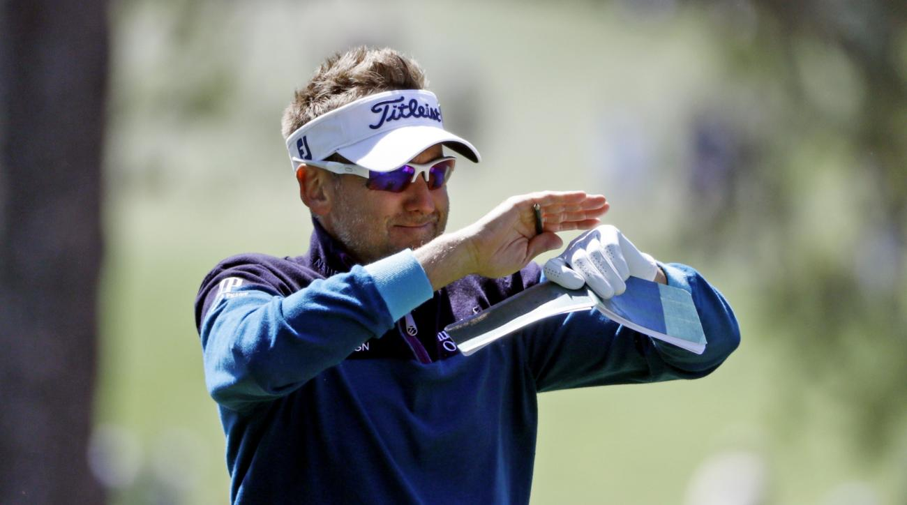 Ian Poulter, of England, shields himself from gusting wind as he examines his course notes on the first fairway during the third round of the Masters golf tournament Saturday, April 9, 2016, in Augusta, Ga. (AP Photo/Jae C. Hong)