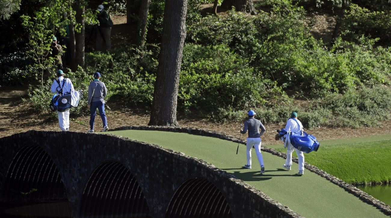 Jordan Spieth, left, crosses over the Hogan Bridge with Rory McIlroy, of Northern Ireland, during the third round of the Masters golf tournament Saturday, April 9, 2016, in Augusta, Ga. (AP Photo/Chris Carlson)