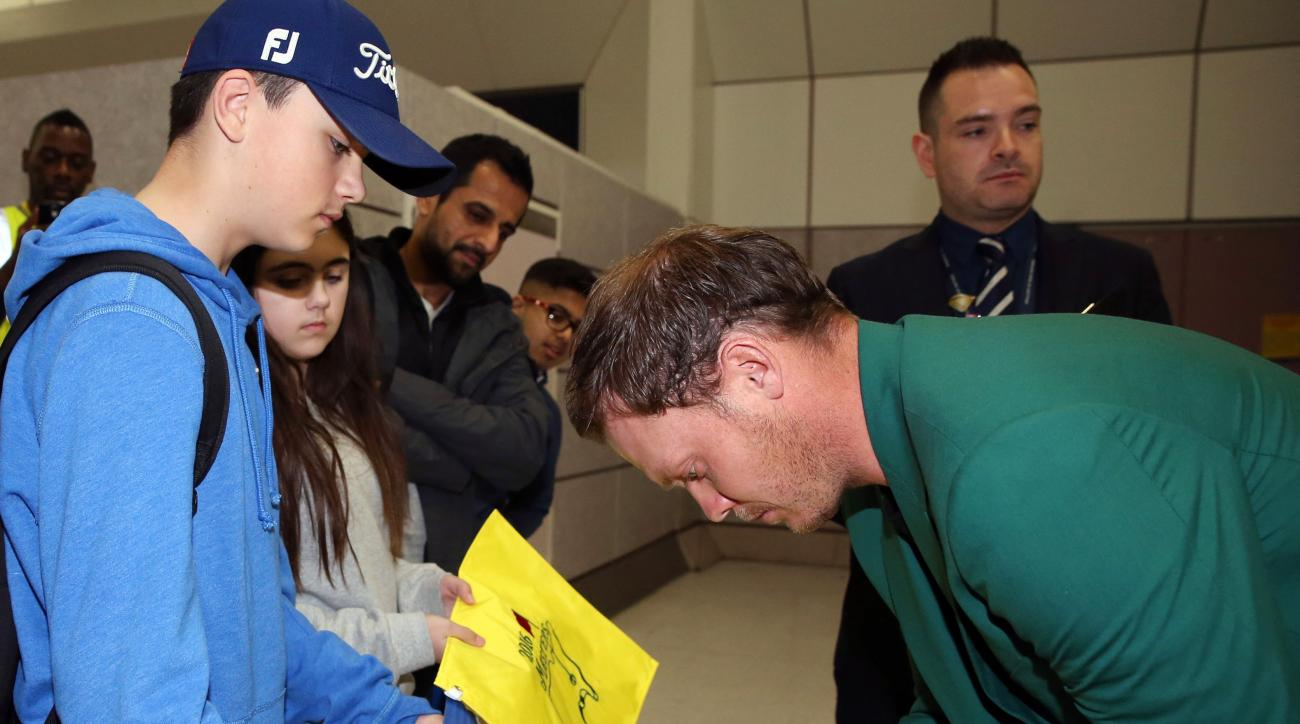 Britain's Danny Willett signs an autographs as he arrives at Manchester Airport, England, Tuesday April 12, 2016, after his victory at the Masters on Sunday. Willett arrived back in Britain having become the first European to win the Masters since 1999 an