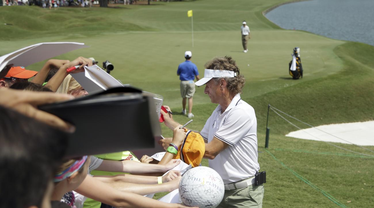 Bernhard Langer, of Germany, signs autographs on the 18th hole during a practice round for The Players Championship golf tournament,  Wednesday, May 11, 2016, in Ponte Vedra Beach, Fla. (AP Photo/Lynne Sladky)
