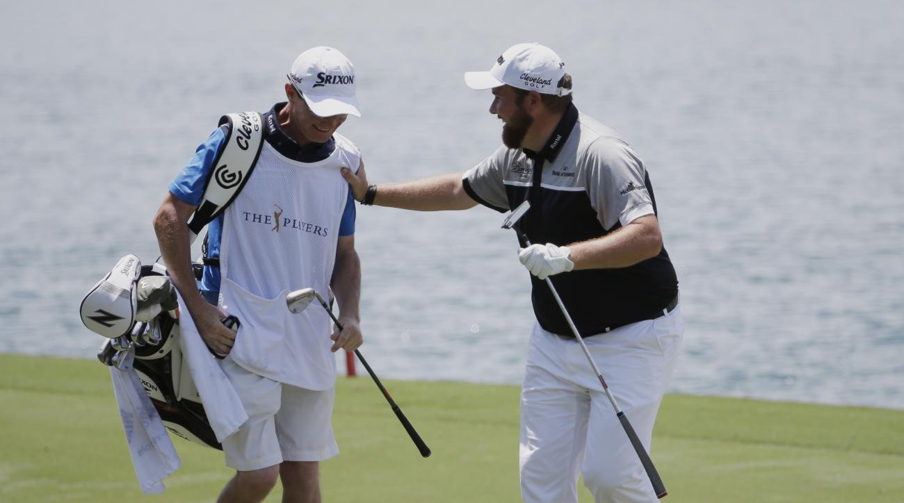 Shane Lowry, of Ireland, reacts to his shot from the 18th fairway with his caddie Dermot Byrne, during the first round of The Players Championship golf tournament Thursday, May 12, 2016, in Ponte Vedra Beach, Fla. (AP Photo/Chris O'Meara)