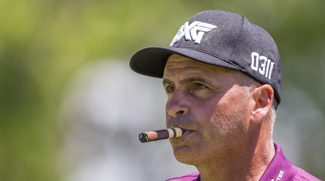 Rocco Mediate smokes a cigar as he looks down the second fairway during the final round of the Senior PGA Championship golf tournament at Harbor Shores Golf Club in Benton Harbor, Mich., Sunday, May 29, 2016. (AP Photo/Robert Franklin)
