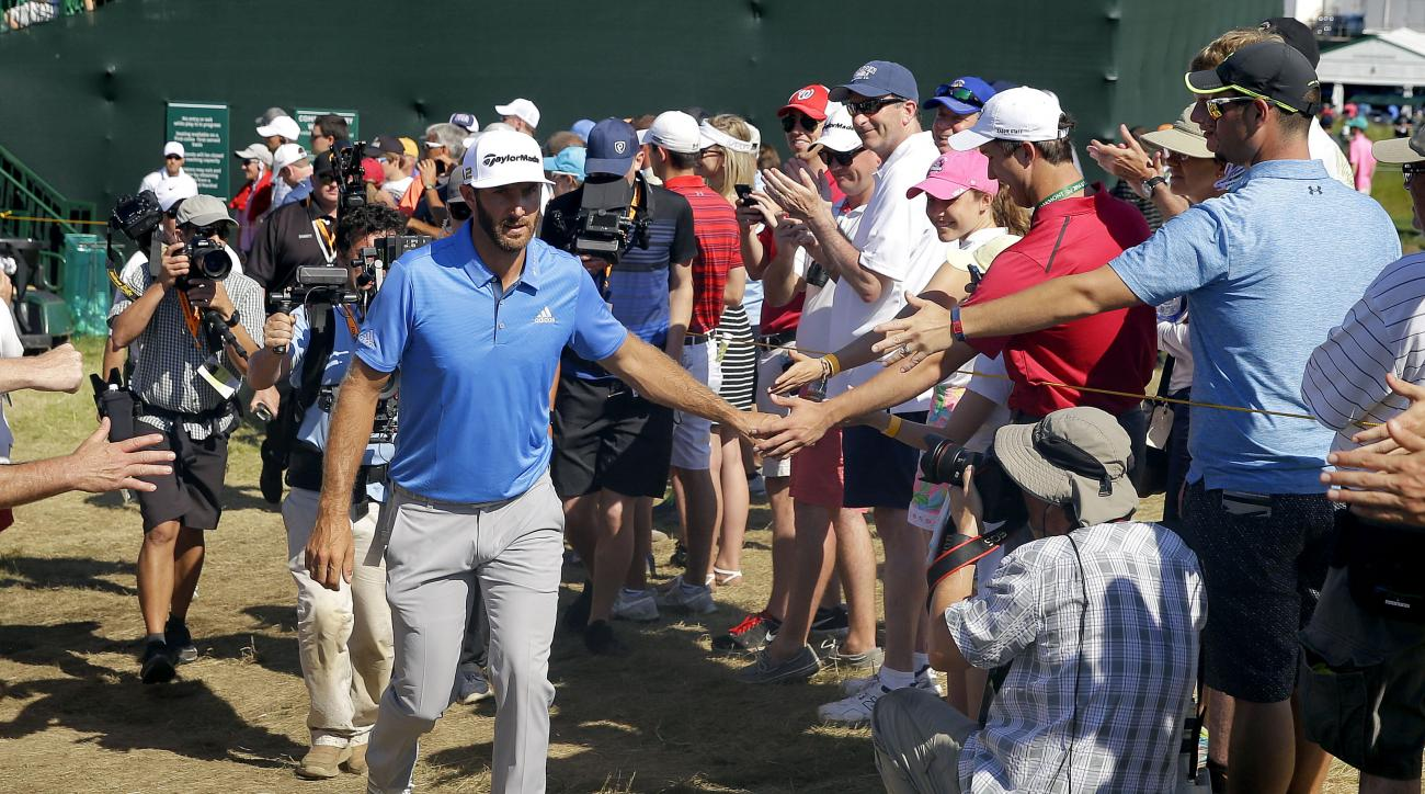 Dustin Johnson greets fans on the way to the 14th tee during the rain delayed second round of the U.S. Open golf championship at Oakmont Country Club on Friday, June 17, 2016, in Oakmont, Pa. (AP Photo/John Minchillo)