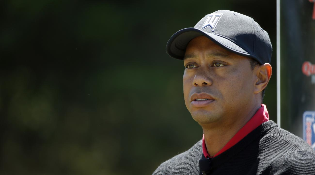 In this May 26, 2016 photo, Tiger Woods pauses during a Quicken Loans National golf tournament media availability on the 10th tee at Congressional Country Club in Bethesda, Md.  Woods on Wednesday, June 22,  says the rules controversy that followed Dustin