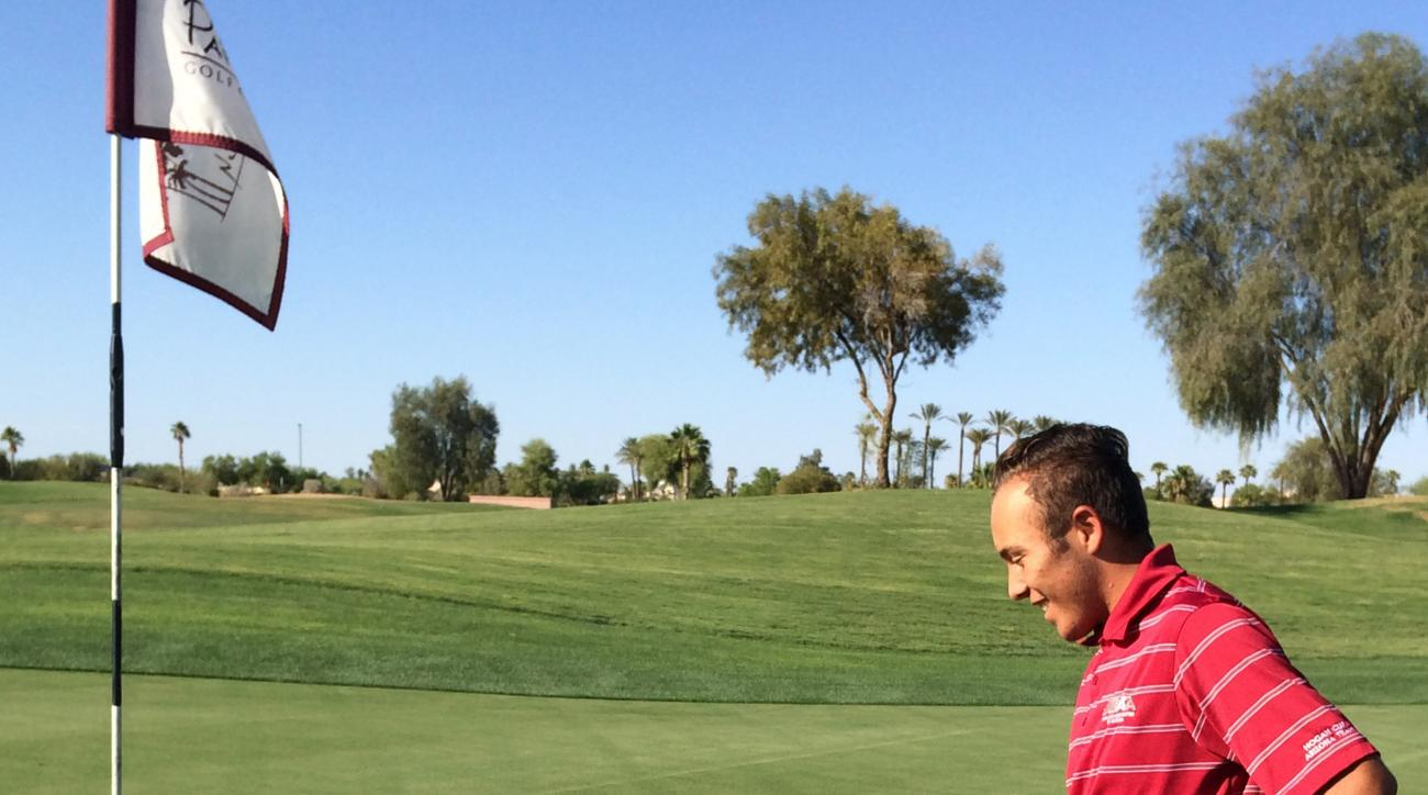 In this photo taken May 13, 2016, Aaron Ramos points to his tee shot on a green at Palm Valley Golf Club in Goodyear, Ariz. Ramos had the closest among 172 shots between six people, including AP Sports Writer John Marshall, as they tried to get an elusive