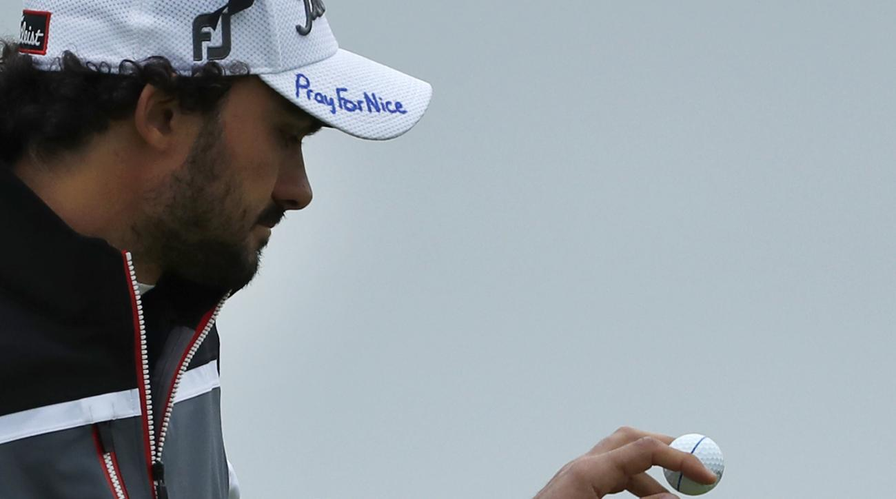 Clement Sordet of France picks up his ball on the 7th green, wearing a cap that has the words 'Pray for Nice' written by hand on it, during the second round of the British Open Golf Championship at the Royal Troon Golf Club in Troon, Scotland, Friday, Jul