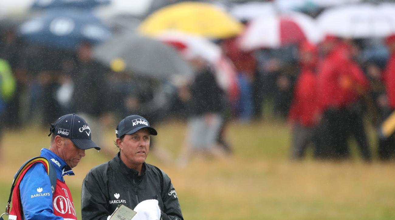 Phil Mickelson of the United States wipes his club as caddie Jim Mckay looks at his notebook as he waits to play from the 16th fairway during the second round of the British Open Golf Championships at the Royal Troon Golf Club in Troon, Scotland, Friday,