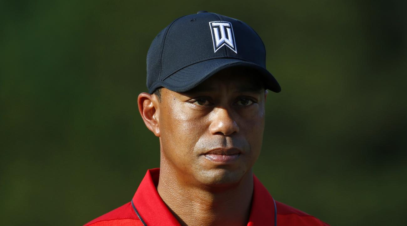 Tiger Woods stands on the 18th green during a trophy ceremony for Quicken Loans National PGA golf tournament winner Billy Hurley III, Sunday, June 26, 2016, in Bethesda, Md. (AP Photo/Patrick Semansky)