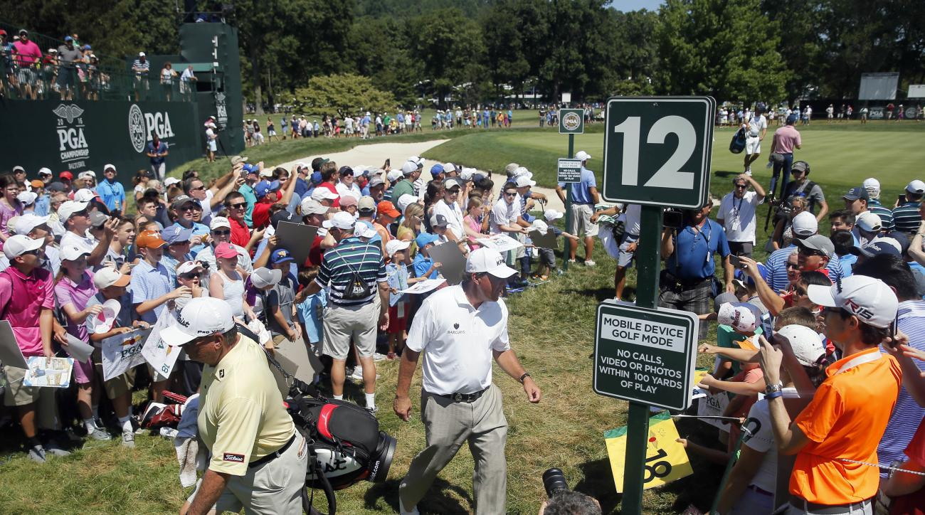 Phil Mickelson signs autographs for fans on the 12 hole during a practice round for the PGA Championship golf tournament at Baltusrol Golf Club in Springfield, N.J., Tuesday, July 26, 2016. (AP Photo/Tony Gutierrez)