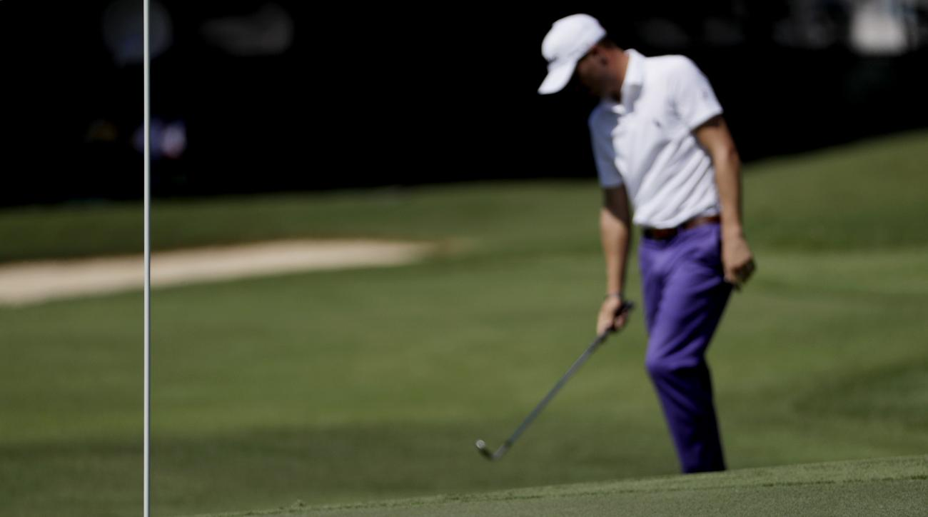 The ball stops short of the hole as Justin Thomas hangs his club after hitting onto the green on the first hole during the first round of the Tour Championship golf tournament at East Lake Golf Club in Atlanta, Thursday, Sept. 22, 2016. (AP Photo/David Go