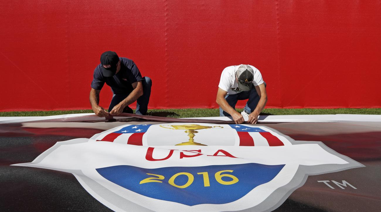 Workers put up bunting on a fence in preparation of the Ryder Cup golf tournament Monday, Sept. 26, 2016, at Hazeltine National Golf Club in Chaska, Minn. (AP Photo/David J. Phillip)