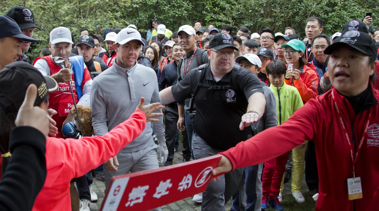 Rory McIlroy of Northern Ireland walks through golf fans after a shot from the bush during the 2016 WGC-HSBC Champions golf tournament at the Sheshan International Golf Club in Shanghai, China, Saturday, Oct. 29, 2016. (AP Photo/Ng Han Guan)