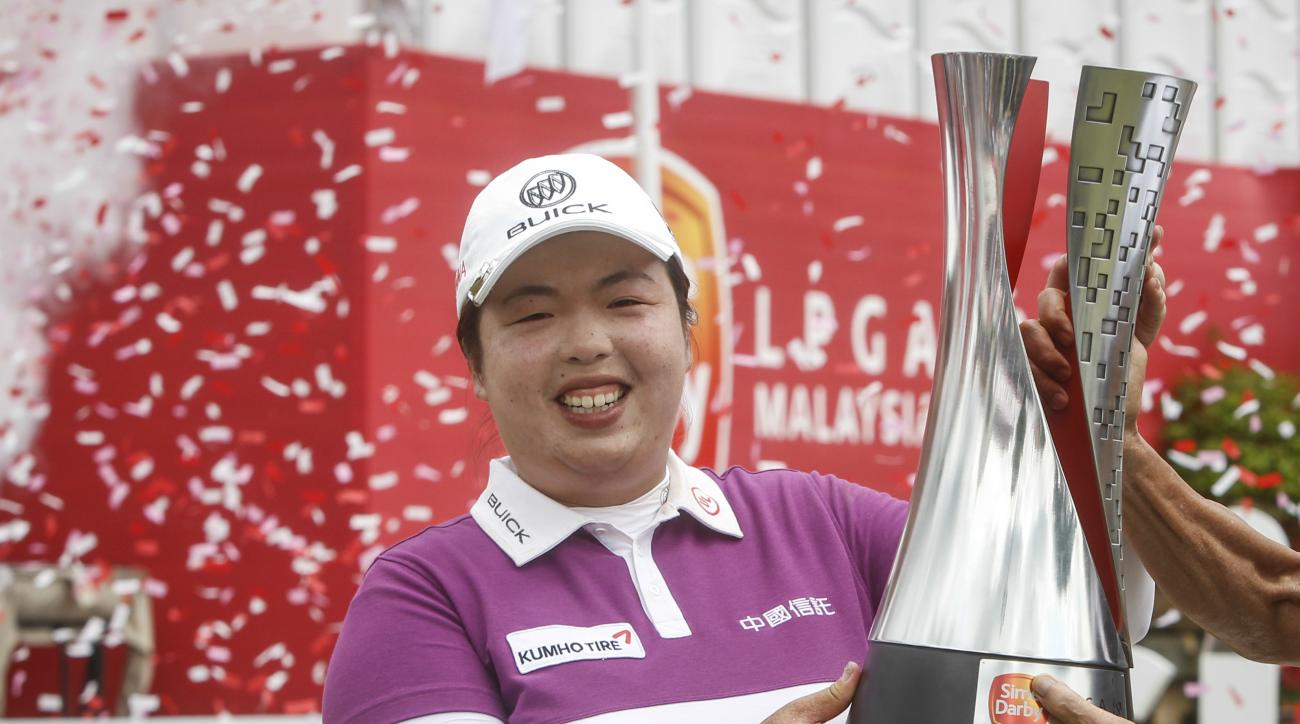 Shanshan Feng of China holds up her trophy after winning the LPGA golf tournament at Tournament Players Club (TPC) in Kuala Lumpur, Malaysia, Sunday, Oct. 30, 2016. (AP Photo/Joshua Paul)