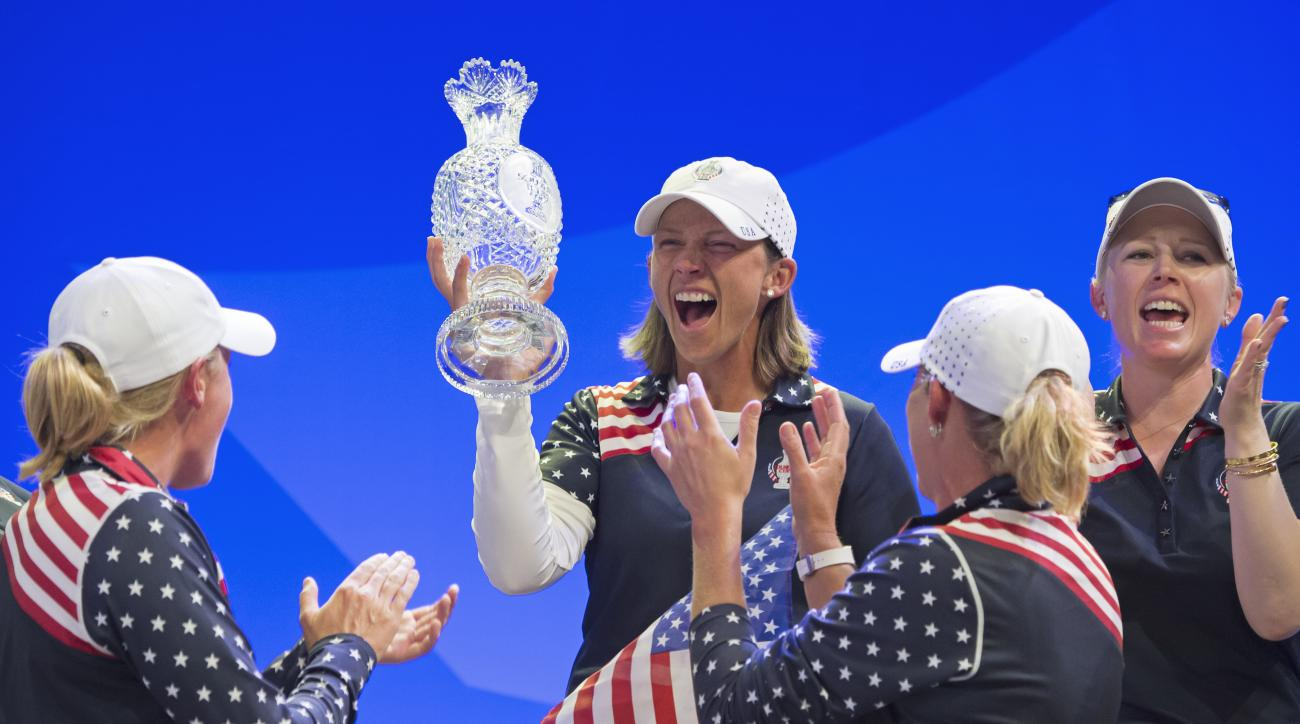 The U.S.  team of United States celebrate with the trophy during the award ceremony at the Solheim Cup golf tournament in St. Leon-Rot, southern Germany, Sunday, Sept. 20, 2015. Paula Creamer defeated Germany's Sandra Gal to complete a remarkable comeback