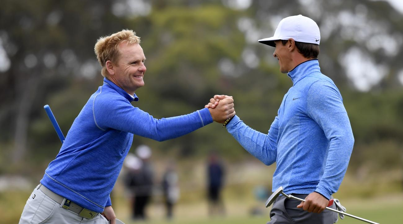 Denmark's Soren Kjeldsen, left, shakes hands with compatriot Thorbjorn Olesen on the 18th green following their match at the World Cup of Golf at Kingston Heath in Melbourne, Australia, Friday, Nov. 25, 2016. (AP Photo/Andrew Brownbill)