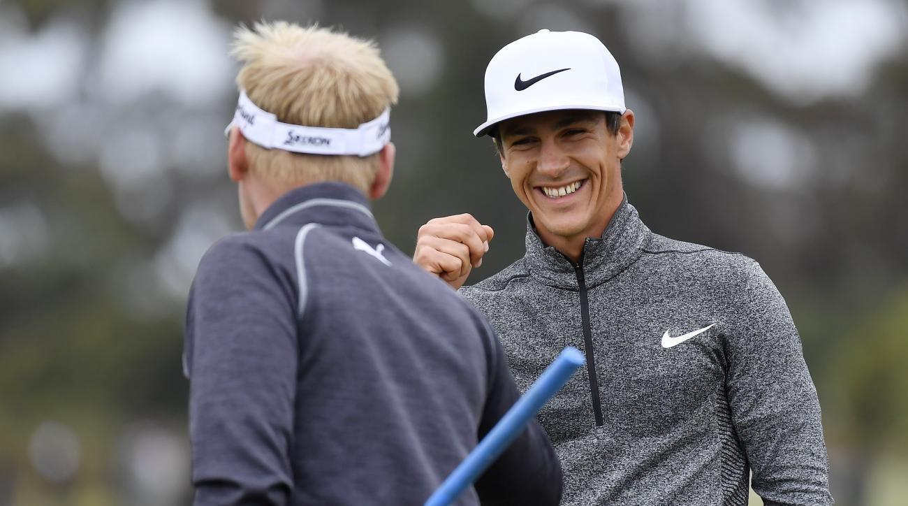 Denmark's Thorbjorn Olesen, right, celebrates with teammate Denmark's Soren Kjeldsen after a birdie putt on the fifth hole during their match at the World Cup of Golf at Kingston Heath in Melbourne, Australia, Saturday, Nov. 26, 2016. (AP Photo/Andrew Bro