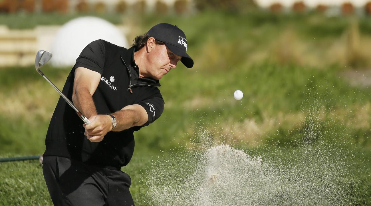 FILE - In a Sunday, Feb. 14, 2016 file photo, Phil Mickelson hits out of a bunker onto the second green of the Pebble Beach Golf Links during the final round of the AT&T Pebble Beach National Pro-Am golf tournament, in Pebble Beach, Calif. (AP Photo/Eric