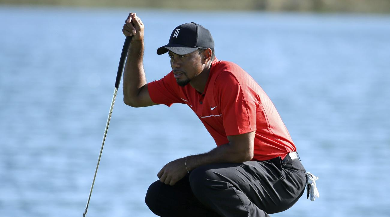 FILE - In this Dec. 4, 2016, file photo, Tiger Woods lines up a putt on the 17th hole during the final round of the Hero World Challenge golf tournament in Nassau, Bahamas.  A new year starts with an old topic, with a twist. Instead of wondering when Tige