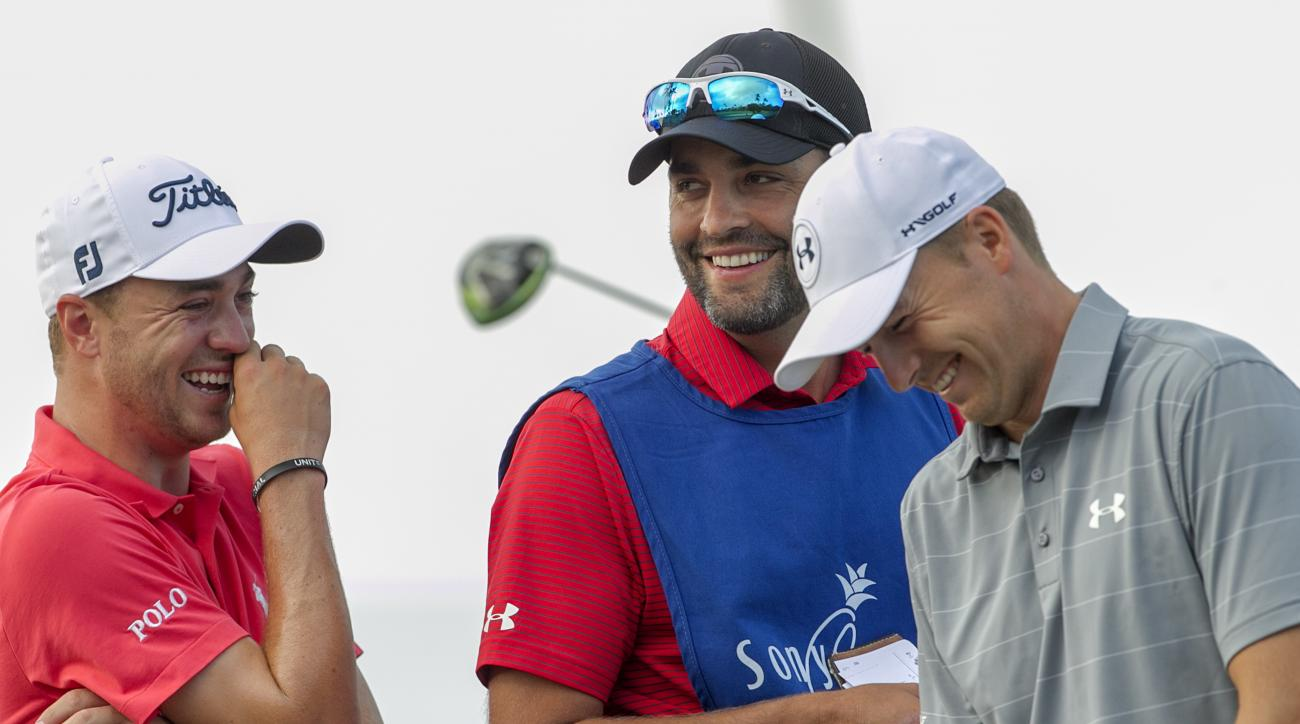 Justin Thomas, left, Michael Greller, center, and Jordan Spieth share a laugh on the 12th green during the first round of the Sony Open golf tournament, Thursday, Jan. 12, 2017, in Honolulu. Greller is Spieth's caddie for the tournament.(AP Photo/Marco Ga