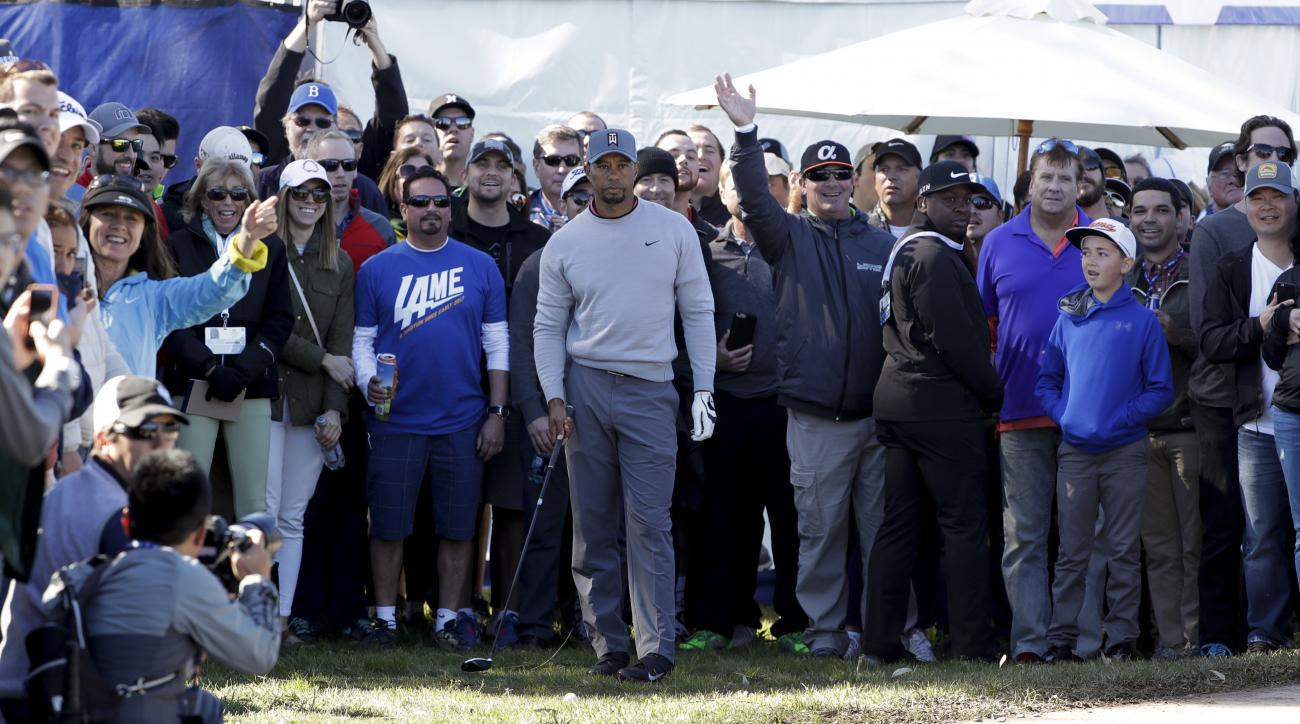 Tiger Woods waits to hit his second shot from the rough alongside a pathway on the 17th hole of the north course during the second round of the Farmers Insurance Open golf tournament Friday, Jan. 27, 2017, at Torrey Pines Golf Course in San Diego. (AP Pho
