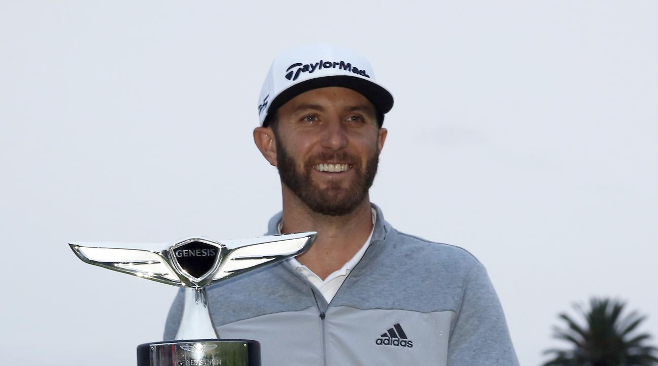 Dustin Johnson poses with his trophy on the 18th green after winning the Genesis Open golf tournament at Riviera Country Club Sunday, Feb. 19, 2017, in the Pacific Palisades area of Los Angeles. (AP Photo/Ryan Kang)