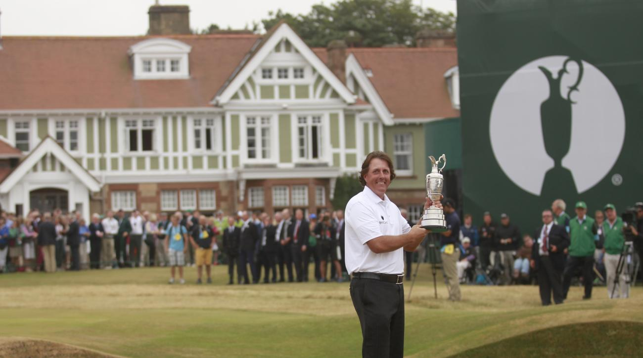 FILE - This is a Sunday July 21, 2013  file photo of Phil Mickelson of the United States holds up the Claret Jug trophy in front of the clubhouse after winning the British Open Golf Championship at Muirfield, Scotland. Muirfield, one of the golf clubs tha