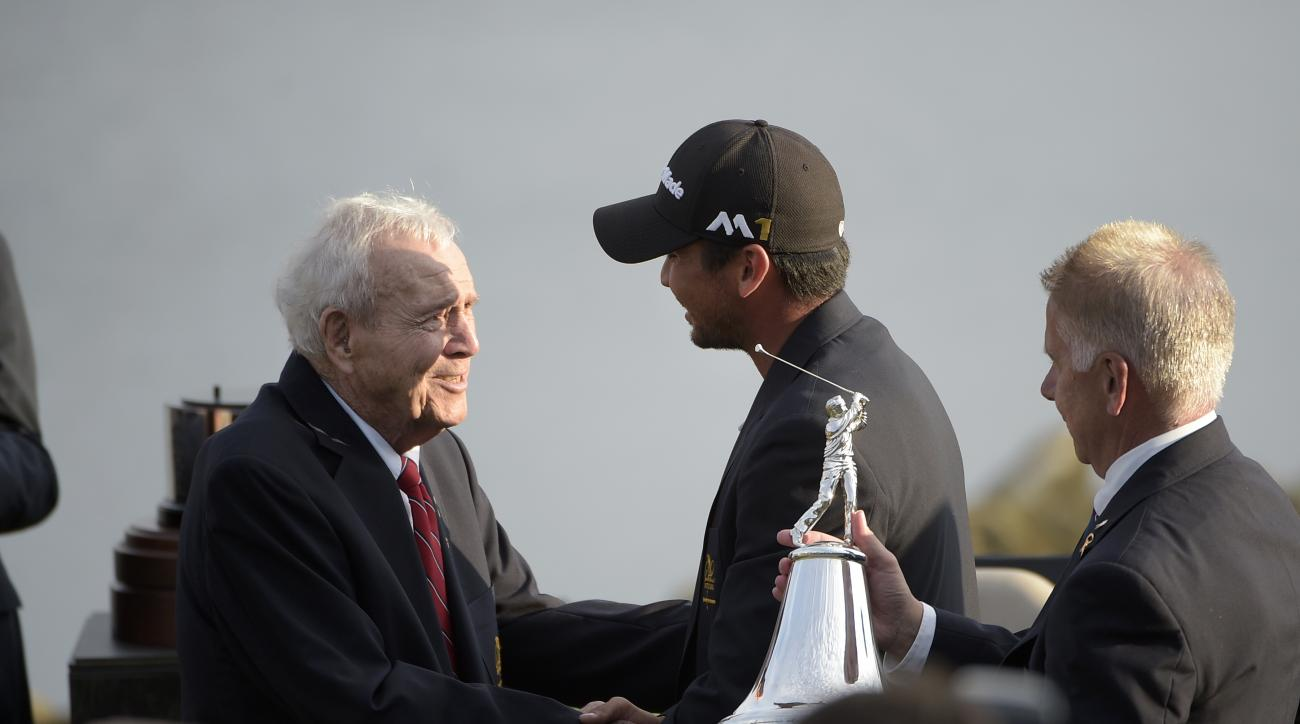FILE - In this March 20, 2016, file photo, Arnold Palmer, left, congratulates Jason Day, center, of Australia, after Day won the Arnold Palmer Invitational golf tournament in Orlando, Fla. (AP Photo/Phelan M. Ebenhack, File)