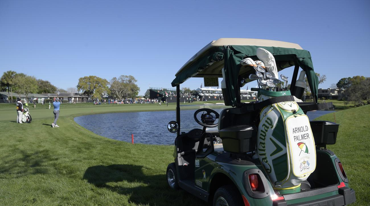 The golf cart and bag belonging to the late golfing great Arnold Palmer sits on a grassy spot next to the 16th tee as Patrick Rodgers hits from the rough alongside the 18th fairway during the first round of the Arnold Palmer Invitational golf tournament i