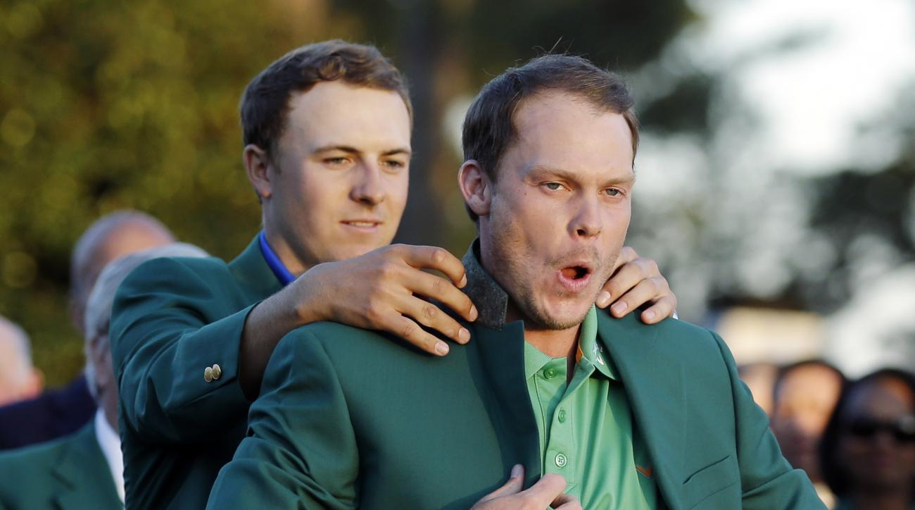 In this April 10, 2016, file photo, defending champion Jordan Spieth, left, helps 2016 Masters champion Danny Willett, of England, put on his green jacket after Willett won the Masters golf tournament in Augusta, Ga. (AP Photo/Chris Carlson, File)