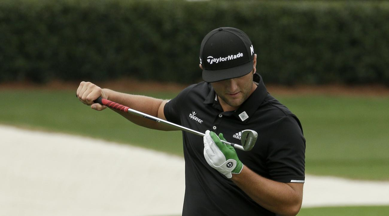 Jon Rahm, of Spain, looks at his club on the driving range during practice for the Masters golf tournament Monday, April 3, 2017, in Augusta, Ga. (AP Photo/Charlie Riedel)