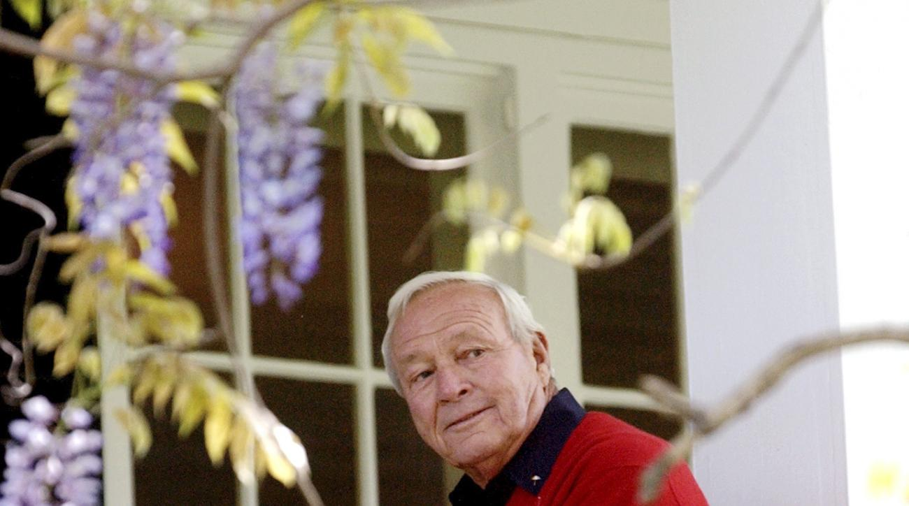 FILE - In this April 5, 2004, file photo, former Masters champion Arnold Palmer sits on clubhouse railing at the Augusta National Golf Club in Augusta, Ga. The King turned up one last time at the Masters, in ill health but still flashing that familiar thu