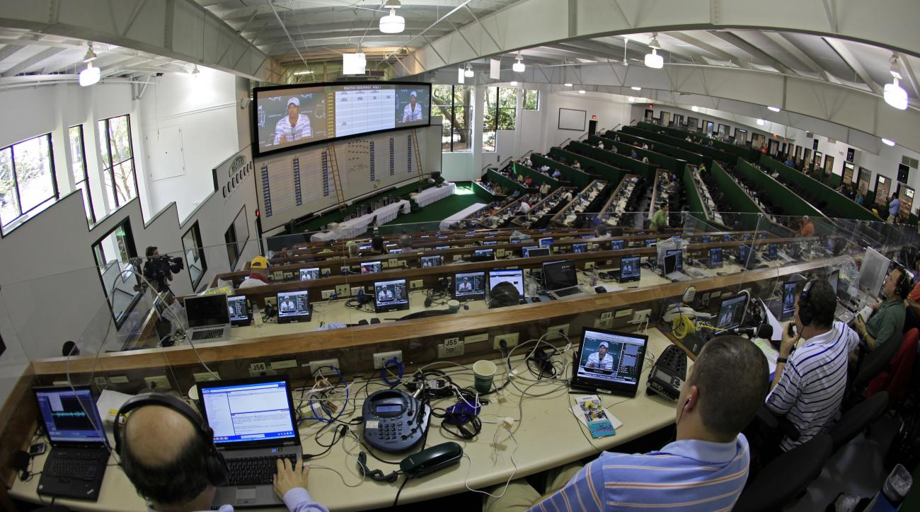FILE - In this April 5, 2010, file photo, members of the media watch Tiger Woods' news conference from the media center at the Masters golf tournament in Augusta, Ga. Covering the Masters is not hard work, not after Augusta National unveiled a new press c