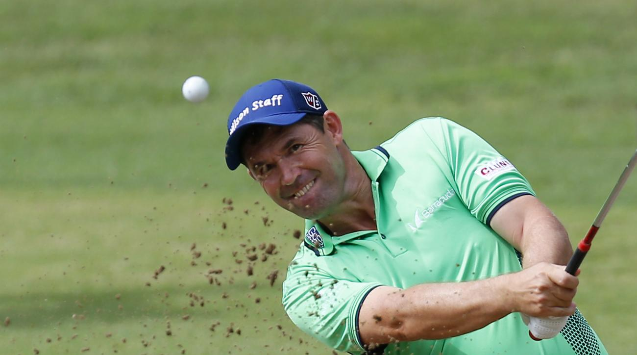FILE - In this Sept. 16, 2016, file photo, Padraig Harrington hits the ball out of a bunker during the 73th Italy Open Golf Championship in Monza, Italy. Harrington was struck in the elbow doing a clinic and received six stiches, causing him to pull out o