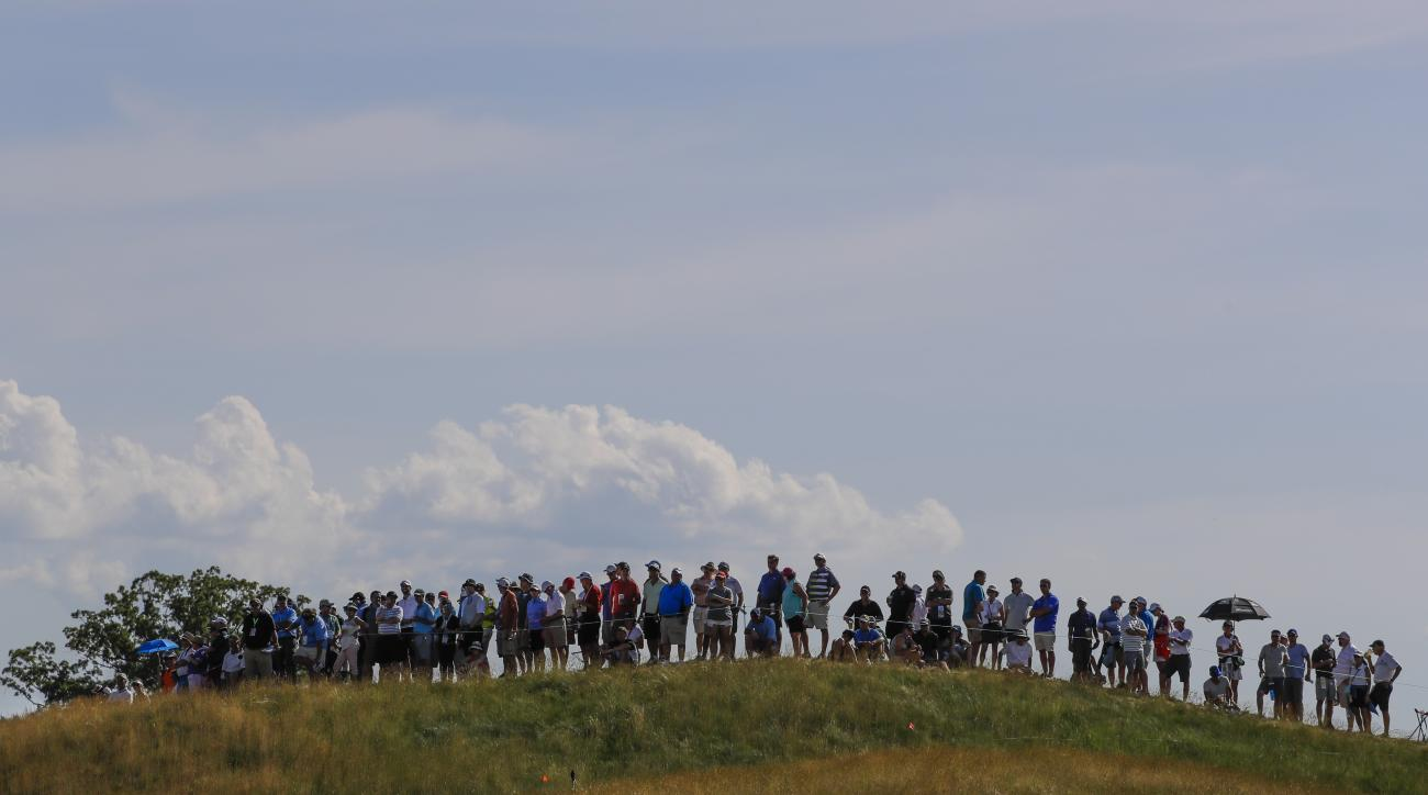 Fans line a hill on the 13th hole during the second round of the U.S. Open golf tournament Friday, June 16, 2017, at Erin Hills in Erin, Wis. (AP Photo/David J. Phillip)