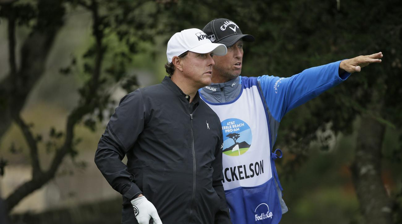 "Phil Mickelson listens to his caddie Jim ""Bones"" Mackay before hitting from the fifth tee of the Monterey Peninsula Country Club Shore Course during the first round of the AT&T Pebble Beach National Pro-Am golf tournament Thursday, Feb. 9, 2017, in Pebble"