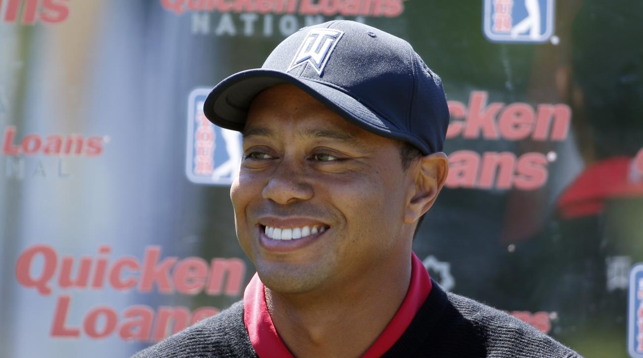 FILE - In this May 16, 2016, file photo, Tiger Woods pauses during a Quicken Loans National golf tournament media availability on the 10th tee at Congressional Country Club, in Bethesda, Md. Tiger Woods' absence from golf isn't just being felt on the cour