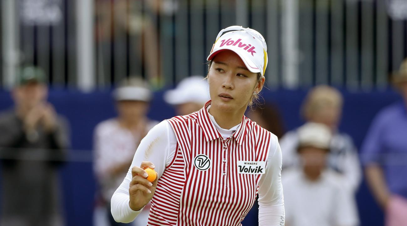 Chella Choi, of South Korea, acknowledges the gallery after making birdie on the 18th green during the third round of the Women's PGA Championship golf tournament at Olympia Fields Country Club, Saturday, July 1, 2017, in Olympia Fields, Ill. (AP Photo/Ch