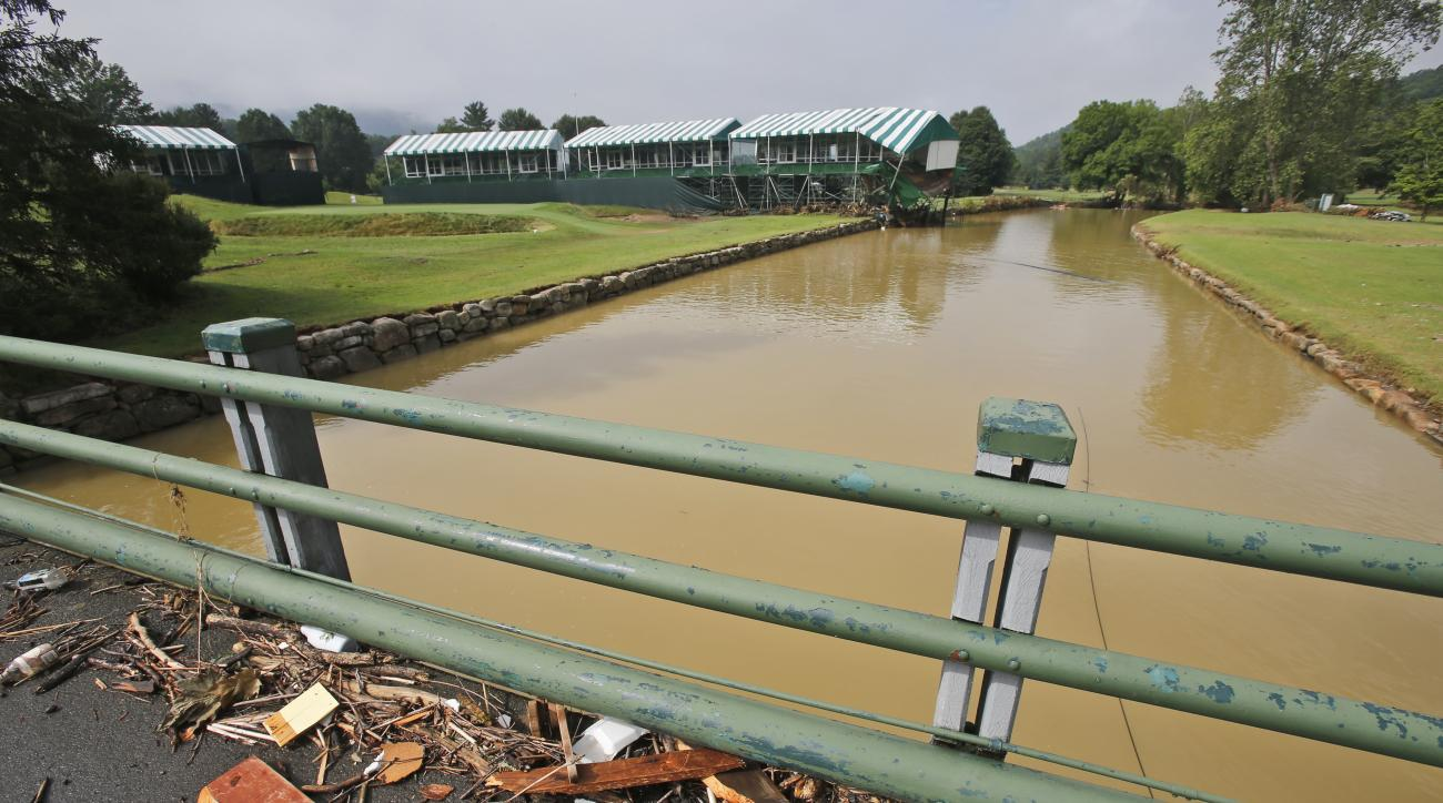 FILE - In this June 28, 2016, file photo, debris from floodwaters litters a pedestrian bridge above Howard Creek along the 18th hole of the Old White Course at the Greenbrier Resort in White Sulphur Springs, W. Va.  Last year's Greenbrier Classic golf tou