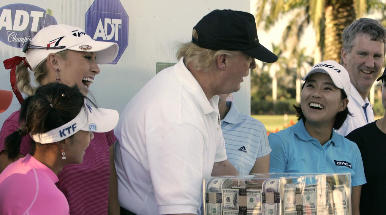 FILE - This Nov. 18, 2006 file photo shows Donald Trump, center, putting his hands on a box of money while posing for a photo with the eight golfers who qualified for the final round following the third round of the LPGA ADT Championship at the Trump Inte