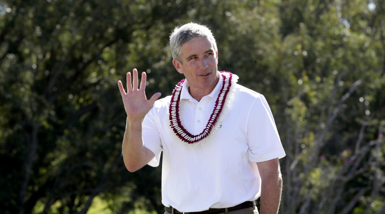 FILE - In this Jan. 8, 2017, file photo, PGA Commissioner Jay Monahan waves to fans before speaking after the final round of the Tournament of Champions golf event, at Kapalua Plantation Course in Kapalua, Hawaii.  In his first year as PGA Tour commission