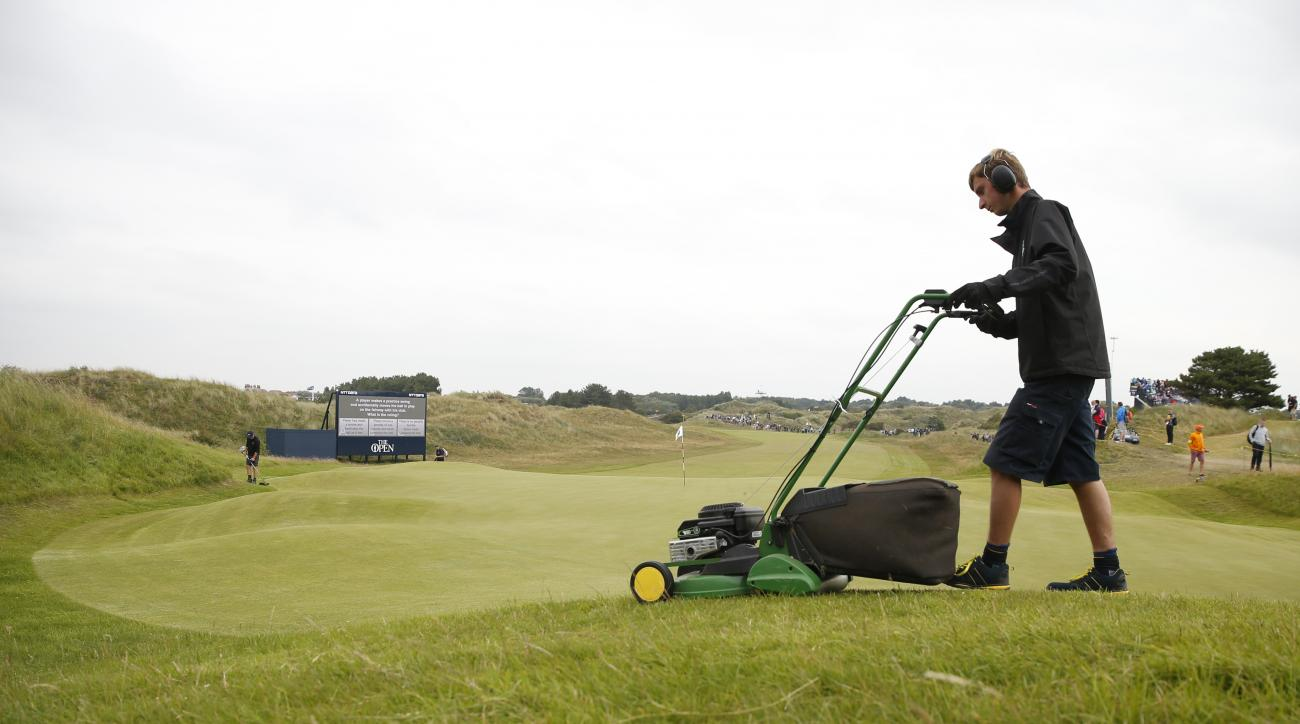 A greenkeeper mows the light rough round the edge of the 6th green during a practice round ahead of the British Open Golf Championship, at Royal Birkdale, Southport, England Wednesday, July 19, 2017. (AP Photo/Alastair Grant)