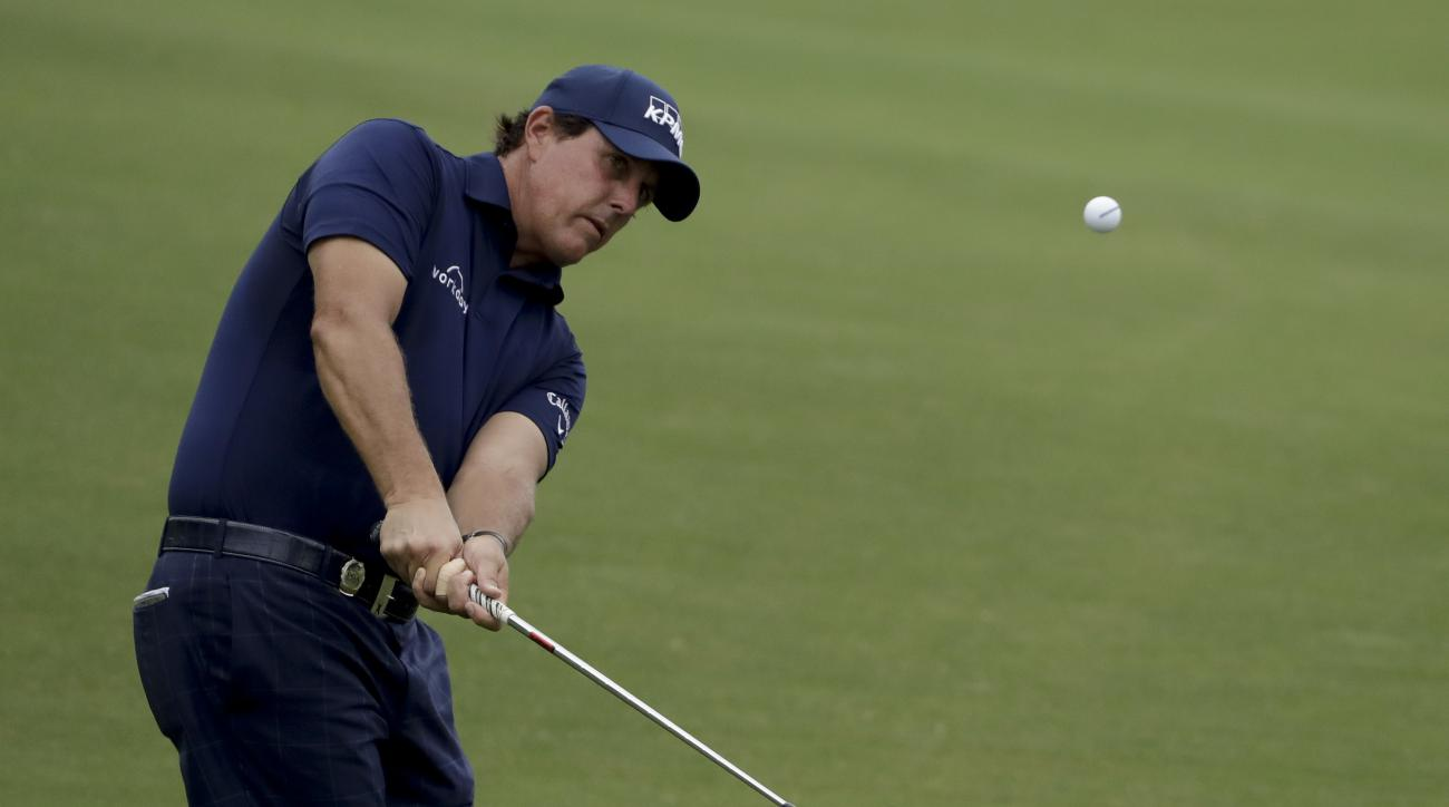 Phil Mickelson chips to the 14th green during the second round of the PGA Championship golf tournament at the Quail Hollow Club Friday, Aug. 11, 2017, in Charlotte, N.C. (AP Photo/Chris O'Meara)